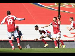 Arsenal's Eddie Nketiah (centre) celebrates after scoring his side's first goal during an English Premier League match against Fulham at the Emirates Stadium in London, England, yesterday.