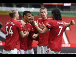 Manchester United's Mason Greenwood (centre) is congratulated by teammates after scoring during their English Premier League match against Burnley at the Old Trafford stadium in Manchester, England, yesterday.