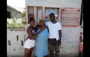Raquel Gayle(centre), the mother of footballer Shamar Nicholson, stands outside her home in Trench Town, St Andrew, with Nicholson's siblings, Shamori Nicholson (right) and Kamoya Leckey.