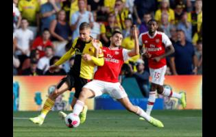 Watford's Gerard Deulofeu (left) vies for the ball with Arsenal's Dani Ceballos during their English Premier League match at the Vicarage Road stadium in Watford, near London, yesterday.