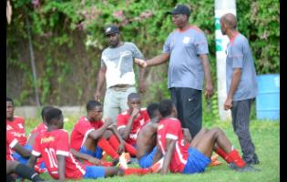 Camperdown High coach Christopher Bender (second right) speaks with his players during the half-time break in their ISSA/Digicel Manning Cup encounter  against Edith Dalton James High at the Alpha Boys Home football field on September 21, 2019.