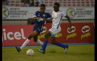 Jamaica College's (JC)  Jonoi Williams (left) challenges McGrath's Nathaniel McKenzie during the ISSA Champions Cup match at the National Stadium on November 2, 2019.