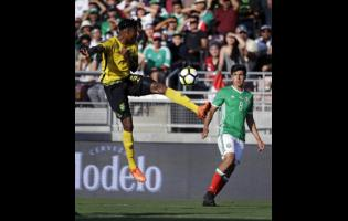 Jamaica's Alvas Powell (left) controls the ball against Mexico's Erick Gutierrez (right) during the first half of a Concacaf Gold Cup semi-final match on July 23, 2017.