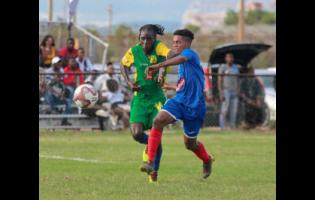 Portmore United's Lamar Walker and Vere United's Devroy Grey tussle for the ball during a Red Stripe Premier League match on September 8.
