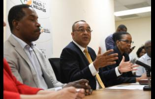 Health Minister Dr Christopher Tufton (centre) speaks at yesterday's press conference at the University Hospital of the West Indies, addressing rumours of a suspected coronavirus case at the institution. Looking on are Dr Carl Bruce (left), medical chief of staff at the UHWI, and Dr Karen Webster-Kerr, acting chief medical officer.