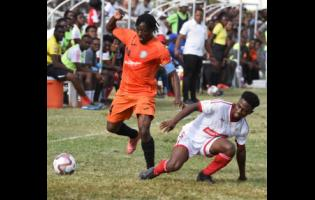Tivoli Gardens captain Kemar Flemmings (left) evades a tackle from Nacquain Brown (right) of UWI FC during a Red Stripe Premier League football match on January 19, 2020.