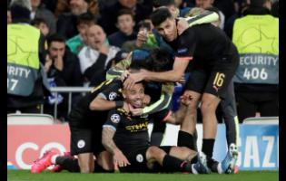 Manchester City's Gabriel Jesus (centre) celebrates with teammates after scoring his side's first goal during the round-of-16 first leg Champions League match against Real Madrid  at the Santiago Bernabeu stadium in Madrid, Spain, yesterday.