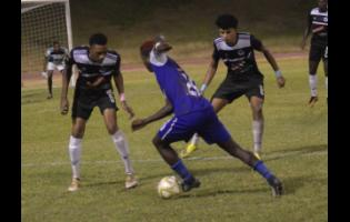Former Cavalier defender Jamoi Topey (left) watches the ball as Reno's Famcy-Hue Stewart (centre) drives forward during a Red Stripe Premier League match at Stadium East in 2018.