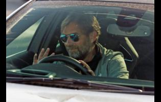 Liverpool manager Jurgen Klopp waves as he arrives at the club's Melwood training ground after the English Premier League announced players can return to training in small groups as the coronavirus lockdown was eased on Wednesday May 20.