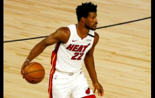 Miami Heat's Jimmy Butler dribbles up court during the first half of an NBA basketball game against the Denver Nuggets, Saturday, August 1, 2020.