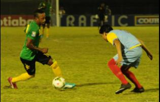 File Jamaica's Under-20 player Junior Flemmings (left) moves away from Aruba's defender Jefferson Vegas in match at the Montego Bay Sports Complex in 2015.