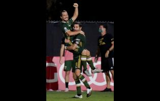 Portland Timbers midfielder Sebastian Blanco, top, celebrates his goal with Diego Valeri against the Philadelphia Union during the second half of an MLS soccer match, Wednesday, Aug. 5, 2020, in Kissimmee, Florida.