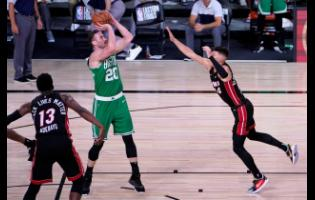 Miami Heat's Bam Adebayo (left) and Tyler Herro defend as Boston Celtics forward Gordon Hayward attempts a shot during the second half of an NBA conference final play-off on  Saturday, September 19.