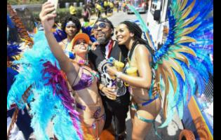 Simone Mahfouz (left) takes a selfie with Machelle Montano  and Kerah Bryant (right) during carnival road march 2018.
