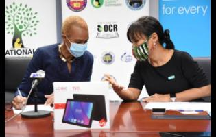 Minister of Education, Youth and Information  Fayval Williams (left) speaks with United Nations Children's Fund Jamaica Country Representative, Mariko Kagoshima, during a ceremony to hand over 534 tablets for students with special needs. The presentation took place at the ministry's Heroes Circle offices in Kingston on Monday.