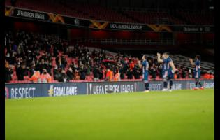 Football fans applaud as the teams enter the pitch for the Europa League Group B  match between Arsenal and Rapid Wien at Emirates stadium in London, England, Thursday, December 3, 2020.