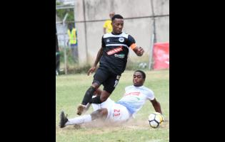 FILE Emelio Russeau, (right) of Portmore United puts in a sliding challenge on Chevone Marsh of Cavalier SC during a Red Stripe Premier League match on Sunday, February 10, 2019.