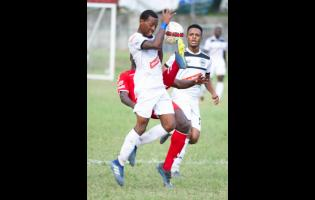 Cavalier's  Chevonne Marsh takes evasive action from a tackle by UWI's Tejuran Williams, who attempts to clear the ball as Alex Marshall looks on, during a Red Stripe Premier League match on December 2, 2018.