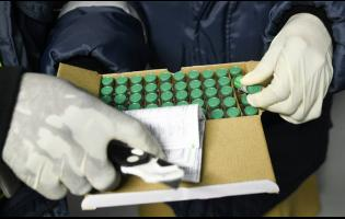 Health officials inspect COVID-19 vaccines at the National Health Fund warehouse after they arrived on Monday.
