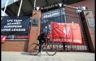 A man cycles past banners outside of Anfield Stadium, Liverpool, England, protesting against the club's decision to join the European Super League yesterday.