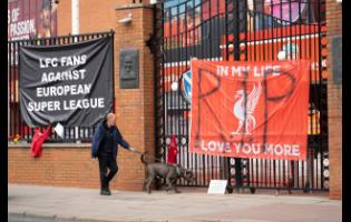 Banners are seen outside Liverpool's Anfield Stadium in Liverpool, England, yesterday after the collapse of English involvement in the proposed European Super League.