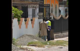 Investigators at the crime scene in Duhaney Park, St Andrew.