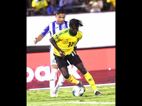 Nicholson (foreground) dribbles ahead of Honduran player Emilio Izaguirre  in their Concacaf Gold Cup match held at the National Stadium on June 18, 2019.