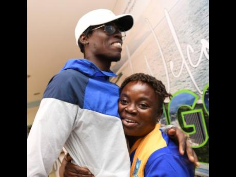 World Championships long jump gold medallist Tajay Gayle is embraced by  Shanikie Osbourne, the head coach at his alma mater Papine High, after he arrived home last night.