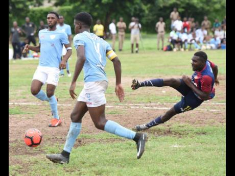 St Andrew Technical's (STATHS) Nicholas Bennett (right) places a shot between St Catherine High pair of Ian Cupee (left) and Isaac Dunkley to score during their ISSA/Digicel Manning Cup  match played at STATHS on October 4. STATHS won 3-0.