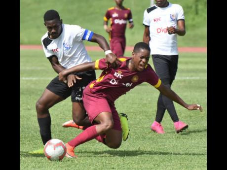 Tarrant High School's Malik Cocking tackles Zhavier Lynch of Wolmer's Boys School in their ISSA/Digicel Manning Cup match at the Stadium East field last Tuesday.