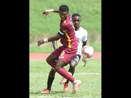 Shamour McLeon (left) from Wolmer's Boys School and Nicholas Johnson from Tarrant High School vie for the ball during their Manning Cup football match. Wolmer's won the match 3-0.