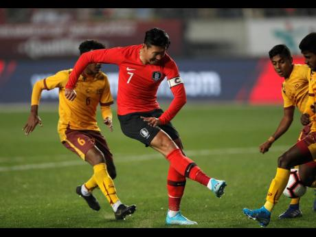 South Korea's Son Heung-min (centre) kicks the ball past Sri Lanka's Mohamed Aman (right) , during their Asian zone Group H qualifying  match for the 2022 World Cup at Hwaseong Sports Complex Main Stadium in Hwaseong, South Korea, on October 10.