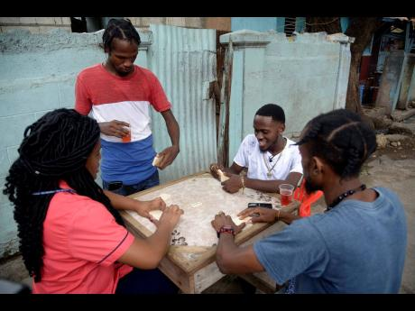 LaaLee (second right) enjoying a game of dominoes with STAR reporter Shereita Grizzle (left) and his friends.