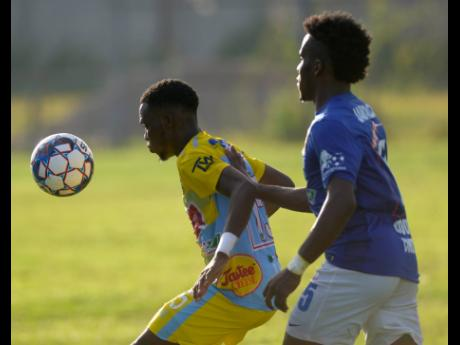 Andre Fletcher (left) of Waterhouse FC shields the ball from Vere United defender Ray Campbell during their Red Stripe Premier League encounter at the Waterhouse Mini Stadium on September 12.