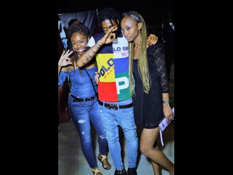 6ix member Daddy 1 is flanked by female fans.