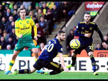 Norwich City's Todd Cantwell (left) scores his side's second goal of the game against Arsenal during their English Premier League match at Carrow Road in Norwich, England, yesterday.
