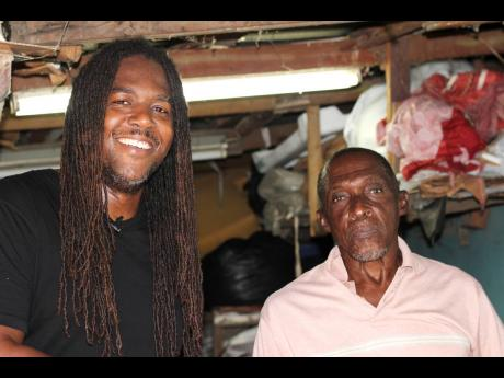 Bay-C shares a moment with Swallowfield resident Mr Campbell, inside his upholstery workshop in Swallowfield, St Andrew.