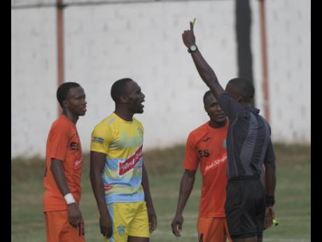 Tivoli Gardens players Rochane Smith (left) and Kemar Flemmings (second right) look on as Waterhouse's Kymani Campbell (second left) is cautioned  by referee Christopher Mason (right) during their Red Stripe Premier League match at the Edward Seaga Sports Complex yesterday.