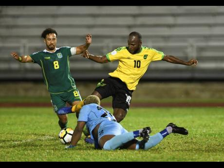 Jamaica's Javon East (right) creates problems for Guyana defender Samuel Cox (left) and goalkeeper Quillan Roberts during a Concacaf Nations League game at the Montego Bay Sports Complex on Monday, November 18, 2019.