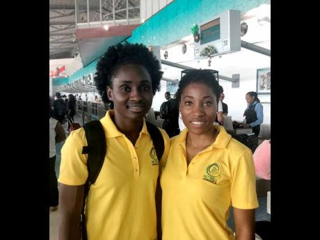 Sunshine Girls Shannika Johnson (left) and Shadian Hemmings at the Norman Manley International Airport yesterday.