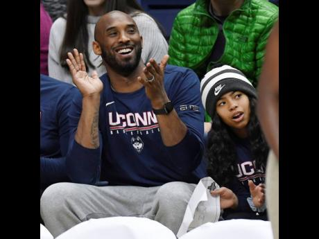 In this March 2, 2019 photo, Kobe Bryant and his daughter Gianna watch the first half of an NCAA college basketball game between Connecticut and Houston in Storrs, Connecticut.