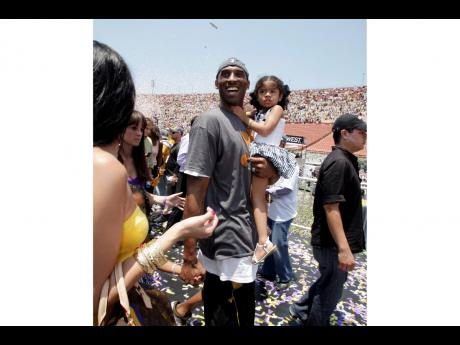 In this June 17, 2009 file photo Los Angeles Lakers' Kobe Bryant smiles as he and his daughter Gianna Maria-Onore walk up the steps after the victory parade celebrating the Lakers' NBA championship in Los Angeles.