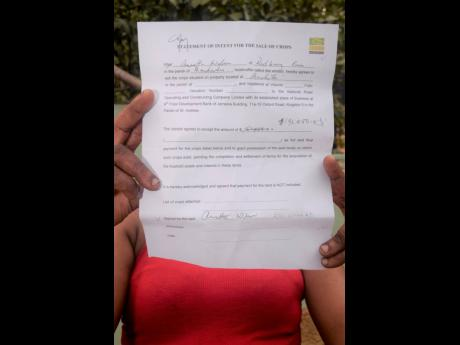 A farmer shows the statement of intent for the sale of her crops.