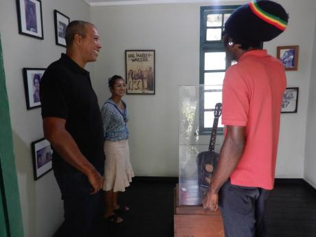 Jermaine Reid (right) speaks with tourists about the negative perception of Trench Town.
