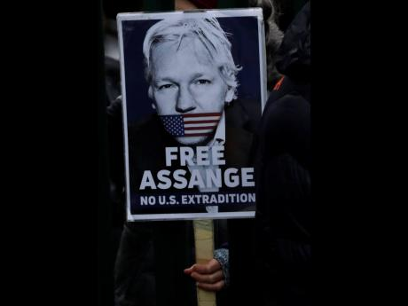 A supporter hold a placard which reads 'Free Assange' as she protests against the extradition of WikiLeaks founder Julian Assange outside Belmarsh Magistrates Court in London on Monday.