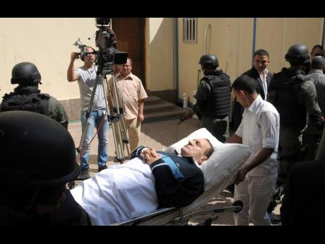 In this 2011 file photo, former Egyptian president Hosni Mubarak lies on a gurney bed while being taken to the courtroom for another session of his trial in Cairo, Egypt. Mubarak, who was ousted in the 2011 Arab Spring uprising, died on Tuesday, age 91.