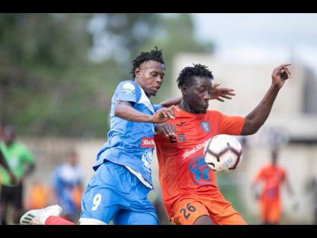 Portmore United's Chavany Willis (left) challenges Tivoli Gardens' Jabeur Johnson for the ball during their Red Stripe Premier League match at the Spanish Town Prison Oval yesterday.