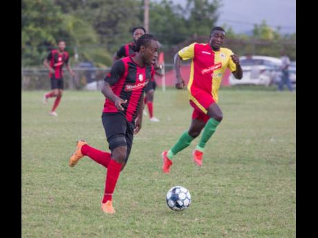 Kemal Malcolm of Arnett Gardens moves away from Humble Lion's Gregory Lewis during their RSPL encounter at Effortville on December 29, 2019.