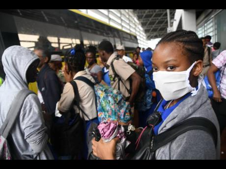 Students wear protective gear against the spread of the novel coronavirus at the Half-Way Tree Transportation Centre on March 11.