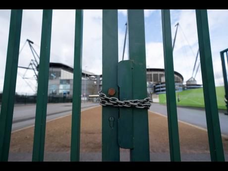 A locked gate is seen by the Etihad Stadium where Manchester City were due to play Burnley in an English Premier League match on Saturday, March 14 after all English games were cancelled due to the spread of the COVID-19 coronavirus.